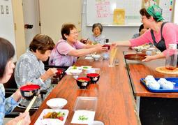 温かいご飯と栄養満点のおかずを笑顔で味わう来場者。家庭での参考にとレシピも一緒に配布される=篠山市本郷