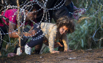 国境線の鉄条網をくぐり、セルビアからハンガリーへと渡る移民ら=2015年(AP=共同)