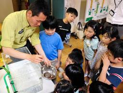 アベサンショウウオの世話について教わる子どもたち=清滝小学校