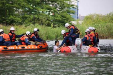 川の中で救助を求める人を助け上げる救助隊員ら=海老名市社家の相模川(同市提供)