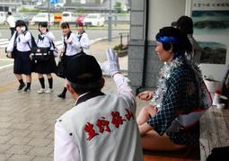 通学する高校生らに対し、手を振って投票を呼び掛けた=JR生野駅前
