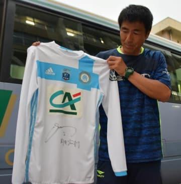 酒井選手から贈られたマルセイユのサイン入りユニホームを手に、エールを送る倉持さん=31日、柏市内