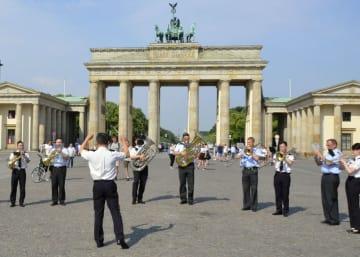 合同演奏会に先立ち、ブランデンブルク門の前で演奏する陸上自衛隊中央音楽隊とドイツ連邦軍の軍楽隊の隊員=1日、ベルリン(共同)