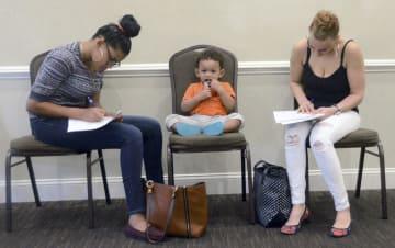 ペンシルベニア州の職探しフェアで申請書に記入する子ども連れの母親ら=15日、マカドー(AP=共同)