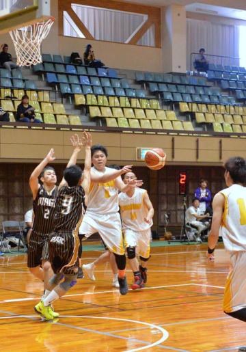 【バスケットボール】ディフェンスの隙を突いてパスを繰り出す選手=県体育館