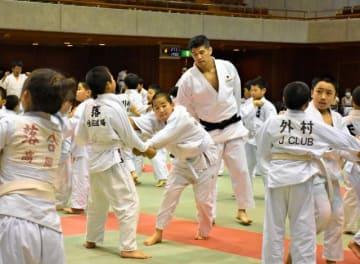 練習に励む児童たちを見守る井上さん=2日午後、宮崎市・県武道館
