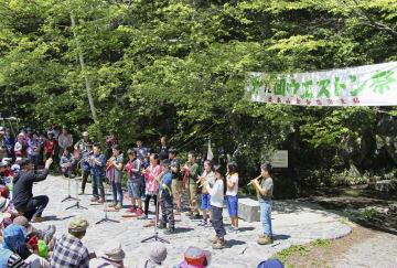 上高地で行われた「ウェストン祭」で、ウェストン碑をバックにリコーダーを演奏する児童たち=3日、長野県松本市