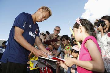 練習場に集まった子どもたちにサインをする、サッカー日本代表の本田圭佑選手(左)=3日、オーストリア・ゼーフェルト(共同)