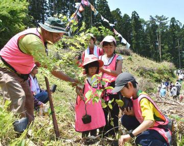 「大きく育って」。青空の下で願いを込めながら植樹する家族連れの参加者