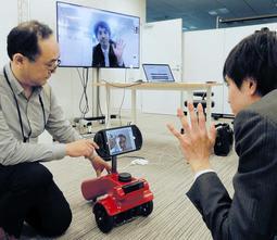 試作ロボを使い、英国にいるクリストファーズさんと会話するスタッフ(右)。ロボが確認したスタッフの映像が奥の大画面で表示される=大阪市北区、ナレッジキャピタル