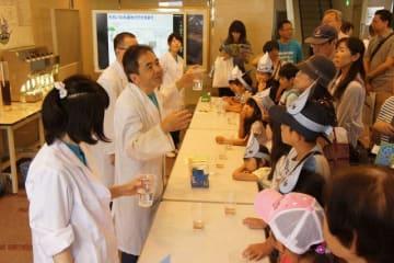 水をきれいにする実験に見入る子どもたち=海老名市社家の県内広域水道企業団社家取水管理事務所