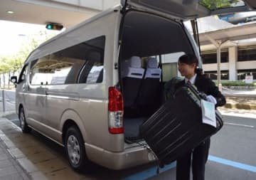 空港で預かった荷物を乗り合いタクシーに積み込むエムケイの乗務員。貨客混載を活用して手ぶら観光を促す(関西空港)
