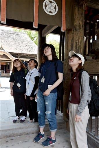 青井阿蘇神社で楼門を見上げる県立大生=人吉市