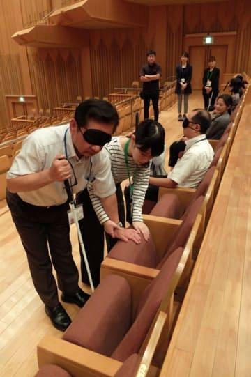 視覚障害者の座席への誘導を学ぶ都城市文化振興財団の職員ら