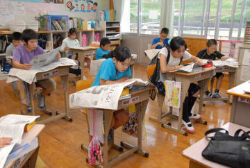 新聞の構成を学び、紙面に目を通す上野小児童