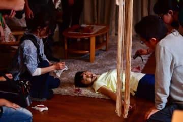 映画「家に帰ると妻が必ず死んだふりをしています。」で死んだふりをしている榮倉奈々さん(中央)