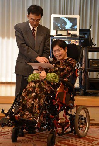 夫の能久さん(左)のサポートであいさつをする佐藤会長