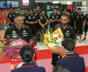 迎の花束を受け取る(左から)ジェイミー・ジョセフヘッドコーチとリーチ・マイケル主将=7日午後、大分空港