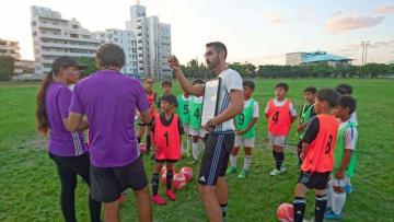沖縄県宜野湾市にあるサッカースクールで子どもたちに指導するレアル・マドリード財団から派遣されたコーチ(グローバルフットボールマネジメント提供)