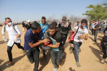 パレスチナ自治区ガザのイスラエルとの境界付近で、負傷した抗議デモ参加者を搬送する人々=8日(ゲッティ=共同)