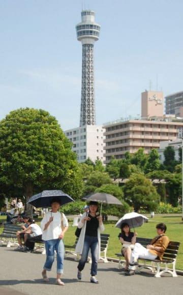 日傘を手に山下公園を歩く観光客ら =横浜市中区