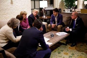G7サミットで議論するカナダのトルドー首相(右から2人目)やトランプ米大統領(中央奥)ら=8日、カナダ・シャルルボワ(ロイター=共同)