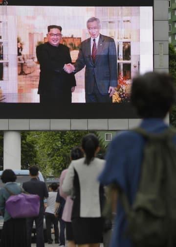北朝鮮の平壌駅近くで金正恩朝鮮労働党委員長のシンガポール訪問を伝えるニュースを見る市民=11日(共同)