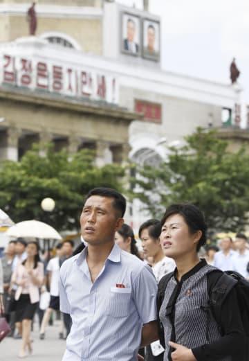 北朝鮮の平壌駅前広場で、金正恩朝鮮労働党委員長のシンガポール訪問のニュースを伝える大型スクリーンを見る市民ら=11日(共同)