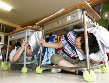 直下型地震を想定した防災訓練で、机の下に避難する児童=12日午前、仙台市宮城野区の幸町南小学校