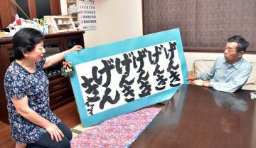 上郷小の児童からの「げんき」と書かれた贈り物を見て当時を振り返る沼倉朝夫さん(右)、恵子さん夫妻