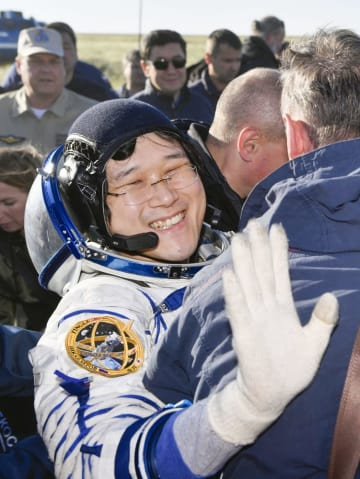 ソユーズ宇宙船でカザフスタンの草原地帯に帰還し、笑顔で手を振る金井宣茂さん