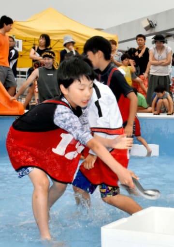 3月末に閉校になった若宮小のプールでウナギのつかみ取りに挑戦する子ども