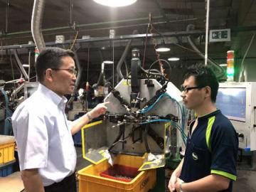 京都銀行の仲介で買収したシンガポールのばねメーカーで、現地の従業員(右)とコミュニケーションを取るマルホ発條工業の幹部