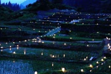 日が沈むと、石垣田のあぜ道に沿って、ろうそくの明かりが浮かび上がった=津南町結東