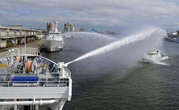 外国漁船を想定した船(右)に放水する水産庁の漁業取締船(手前)と海上保安庁の巡視船=13日午後、新潟市