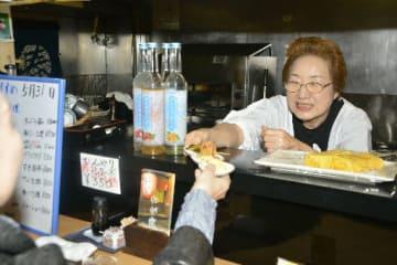 閉店当日、笑顔で接客する貝吹憲子さん。「お客さんに感謝」と万感の思いに浸る=5月31日、八戸市六日町の「肴町のわが家」