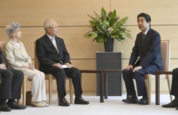 安倍首相(右)と面会する拉致被害者家族会の飯塚繁雄代表。左は横田早紀江さん=14日午後、首相官邸