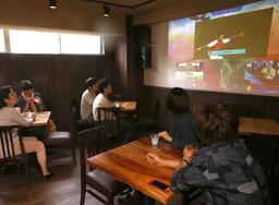 「eスポーツ」を観戦できるバーで、コナミのサッカーゲームソフト「ウイニングイレブン」の大会映像を楽しむ人たち=神戸市北区有馬町、バル・デ・ゴザール(撮影・辰巳直之)
