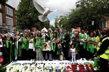 14日、1年前に火災が起きた英ロンドンの高層住宅近くで、犠牲者を追悼し、ハトを放す人々(ロイター=共同)