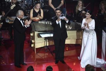 14日、スウェーデン・ストックホルムで開かれたポーラー音楽賞の授賞式で、カール16世グスタフ国王(左)から記念の盾を受け取ったアフガニスタン国立音楽学院のアフマド・サルマスト校長(中央)(AP=共同)