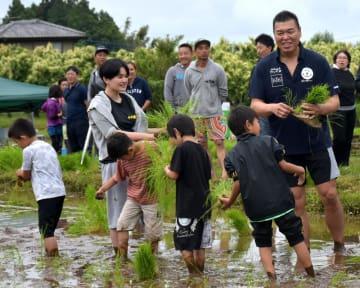 子どもたちと田植えを楽しむ小川直也さん(手前右)=茨城町木部