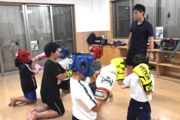 渡辺裕貴さん(右)の指導を受けボクシングの練習に励む子どもたち=土浦市右籾