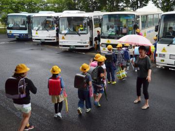 スクールバスに乗り込む児童たち=河内町長竿の町立かわち学園