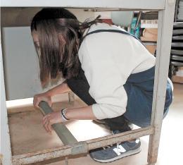 防災無線を聞いて机の下で身を守る遊覧船乗り場の社員