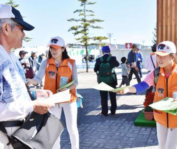 2016年10月の岩手国体開会式で、会場案内などを配るボランティア。スポーツ大会でボランティアが果たす役割は大きい