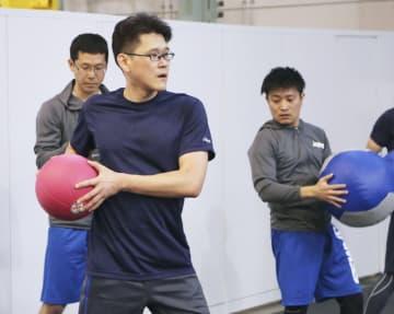 リハビリでボールを使った運動をする宇宙飛行士の金井宣茂さん(手前)=15日午後、茨城県つくば市