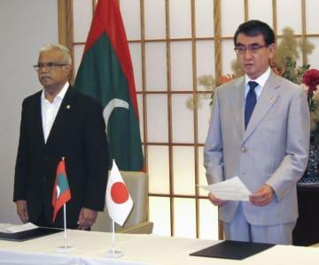 モルディブのアーシム外相(左)と協力文書に署名後、あいさつする河野外相=15日、外務省