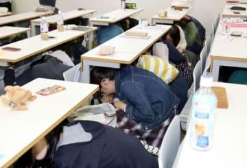 地震を想定した訓練で机の下に入る新潟大の学生=15日、新潟市西区