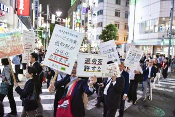 働き方改革関連法案に盛り込まれた高プロに反対し、「過労死許すな」などと書かれたプラカードを手にデモ行進する人たち=15日午後、東京・新橋
