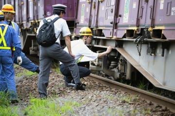 脱線したコンテナ貨車の台車周辺を調べる関係者=16日午後4時39分、千葉市中央区